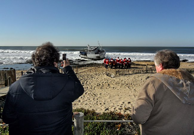 Duas senhoras em primeiro plano, uma delas a tirar fotografias com telemóvel. Ao fundo, a traineira ainada dentro de água e na praia um grupo de bombeiros a discutirem as operações