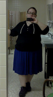 The author wearing a black 3/4 sleeve hooded shirt with white drawstring & buttons, with a purple flowy skirt that covers her knees.  Black running shoes.  Holding on to the wall for balance