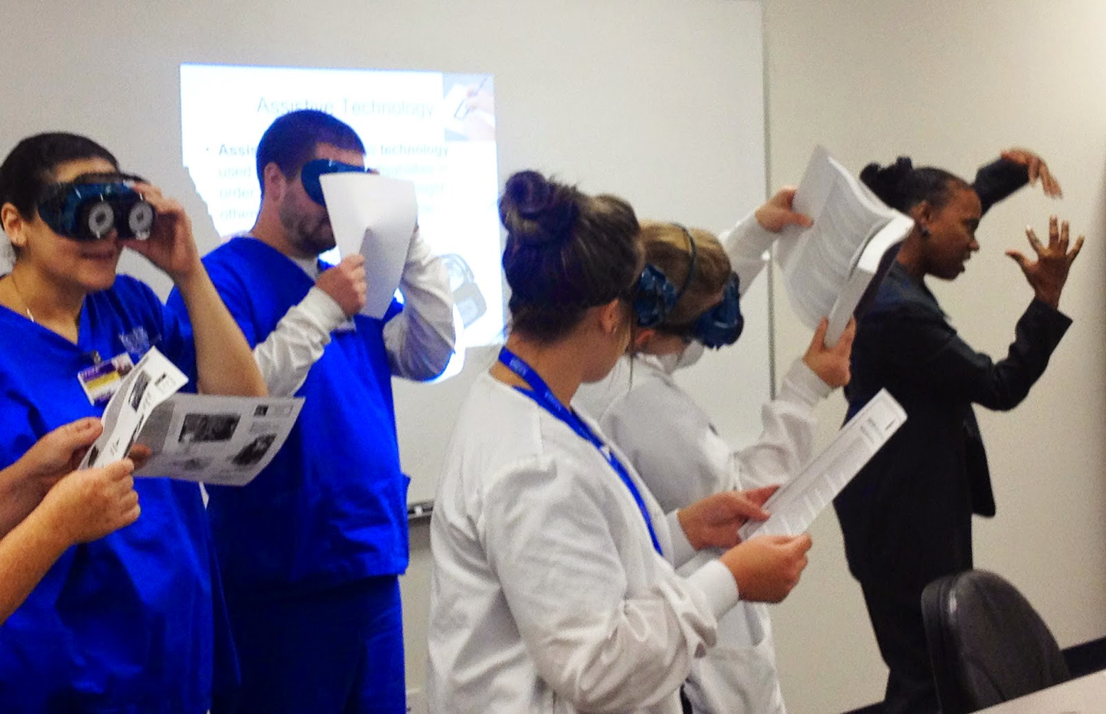 In a lecture room with a whiteboard in the background, Tiffany wearing a dark blazer, uses her hands to emphasize a talking point while OT students wearing blue scrubs try on different sight simulators over their eyes to simulate what it's like with different types of vision loss.