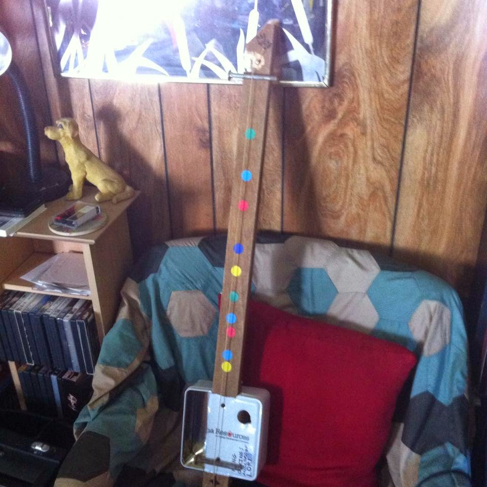A one string guitar made from a cookie tin