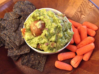 A bowl rockin' guacamole with blue corn chips and baby carrots on the side