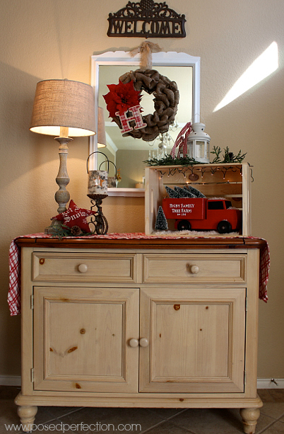 A made over red vintage truck with Christmas trees is the star of this wintery entryway table