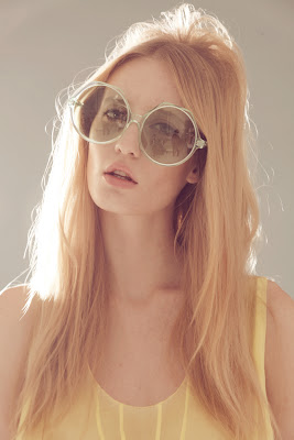 woman wearing huge vintage sunglasses, 60's makeup and hair