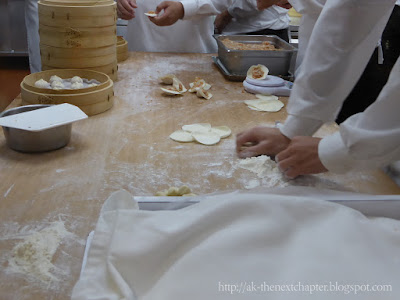 closeup of hands rolling out dumpling dough and someone else filling the dumplings with meat