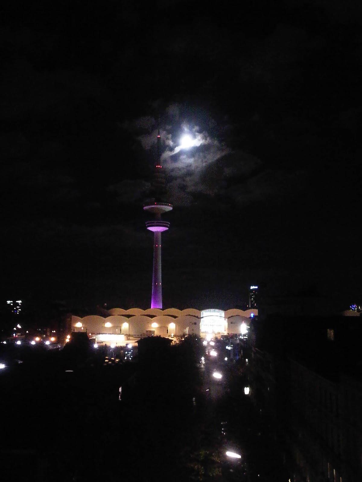 Fernsehturm und Messehallen mit Mond von Wolken verdeckt