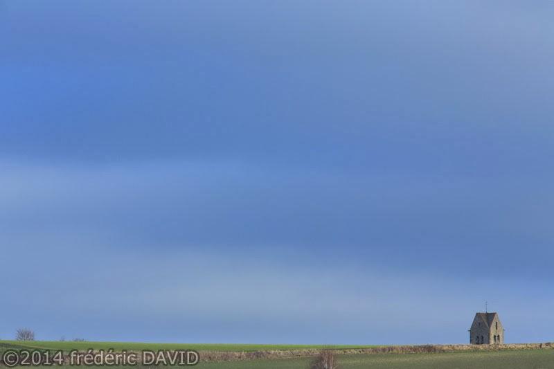 clocher champ ciel sombre nuages