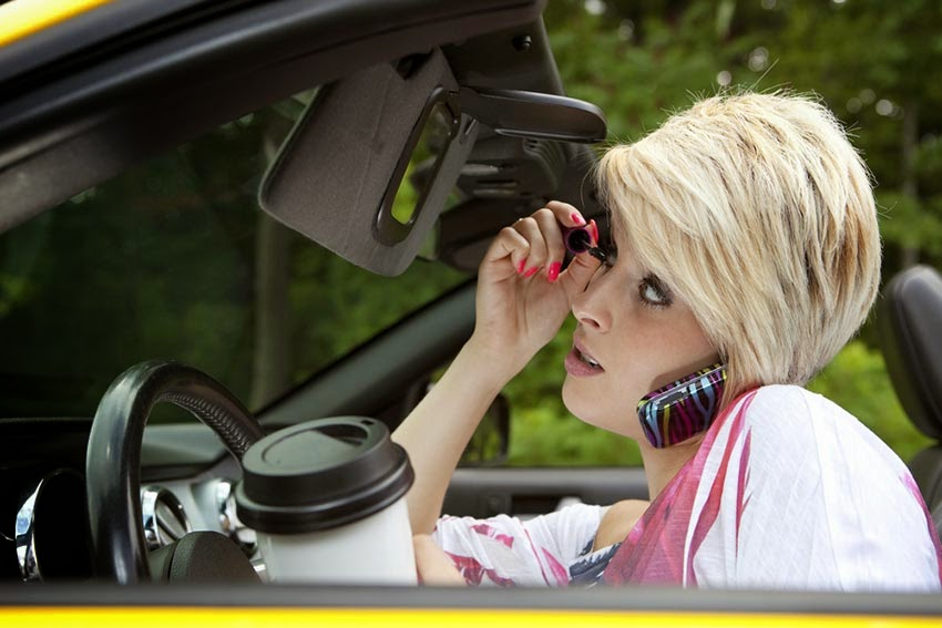 Woman distracted driving doing makeup mobile phone