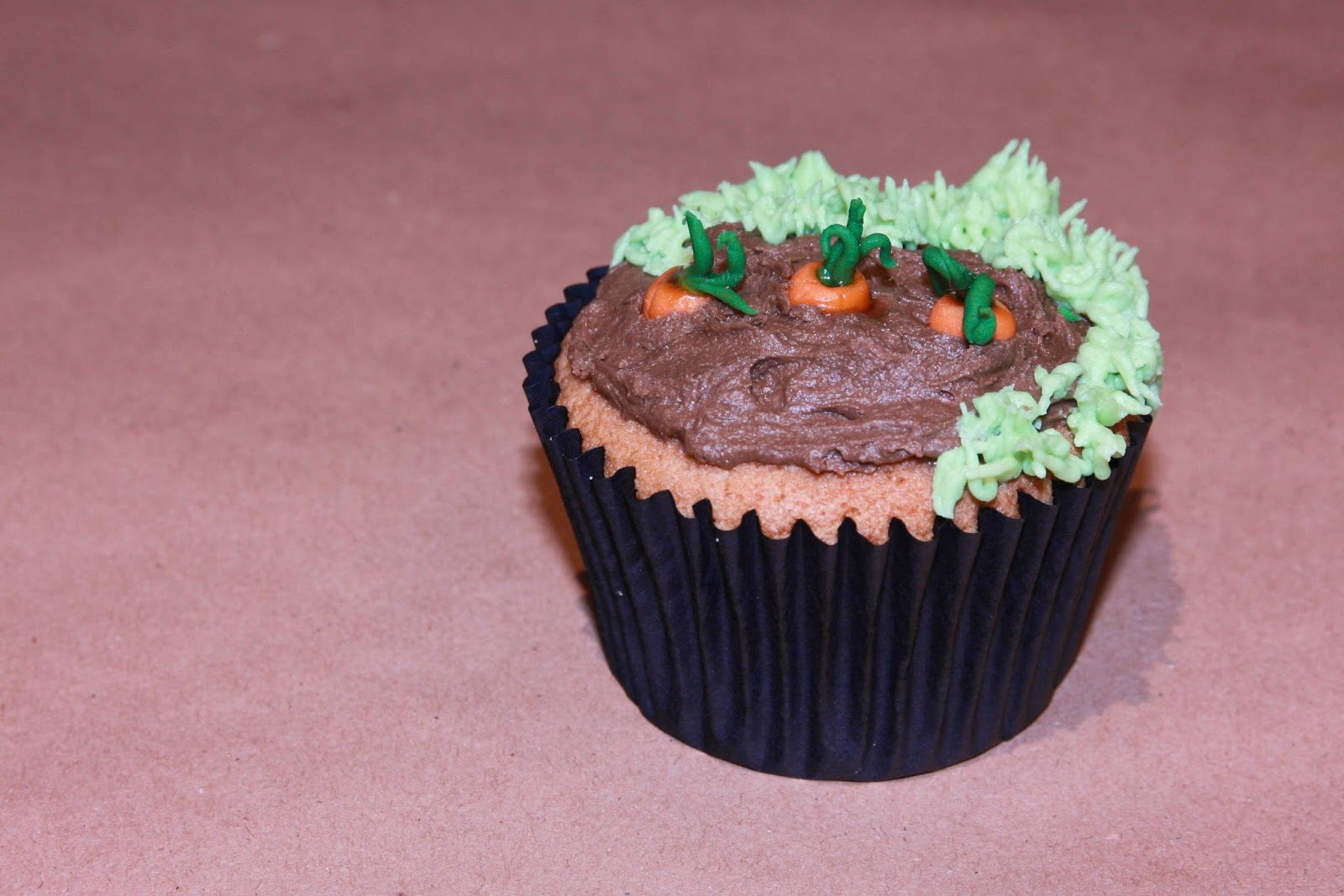 Earl Grey cupcake decorated with carrots growing in a vegetable patch