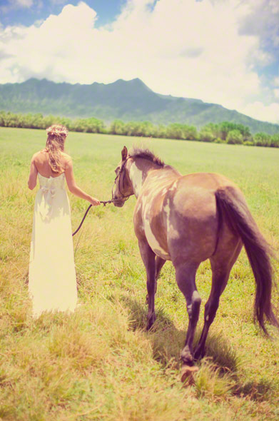 bride walking in a field on kauai after her wedding ceremony at a destination hawaii wedding