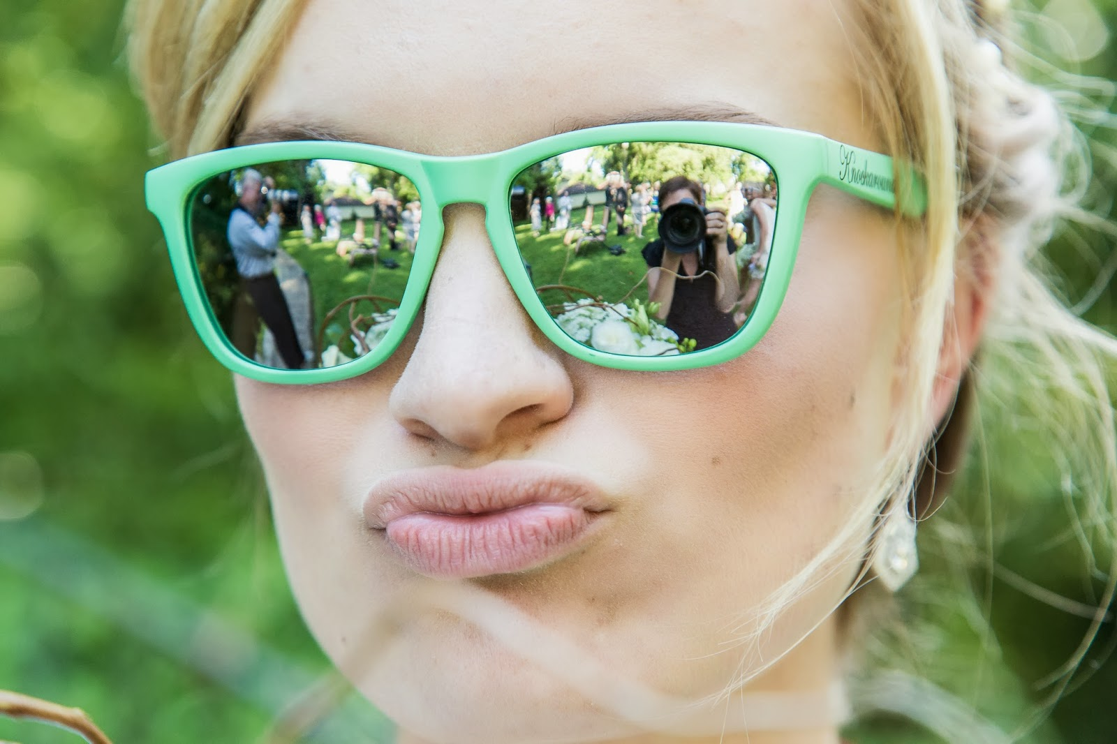 bride wearing mint green sunglasses, reflection of photographers in sunglasses