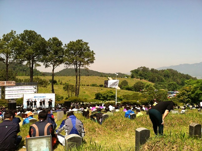 image of grassy cemetery on hill.  Many people sitting amongst rows of cemetery