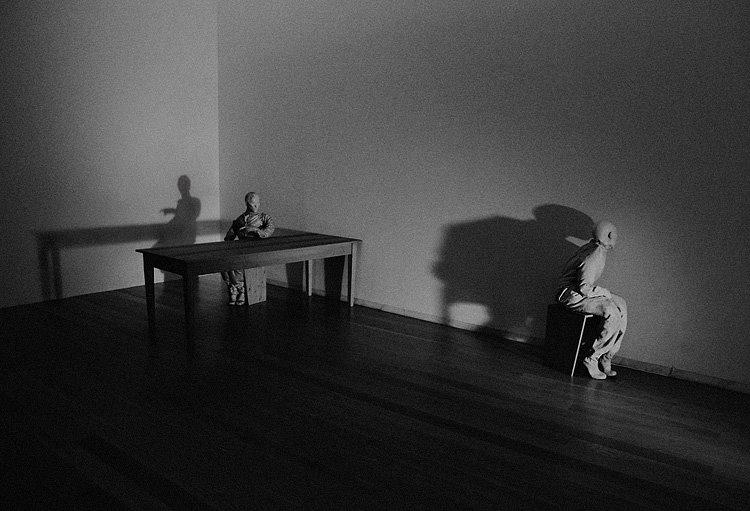 Sala com uma mesa e uma figura em posição dar ordens e em frente outra figura, sentada num banco e virada contra a parede, come se estivesse de castigo. Iluminação frontal, muito dura e projectando grandes sombras, conferindo uma atmosfera muito dramática
