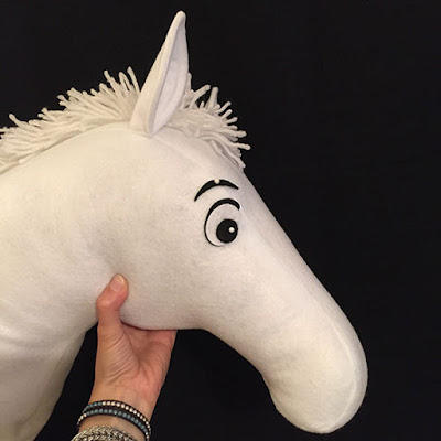 White horse head made out of felt with white yarn for a mane