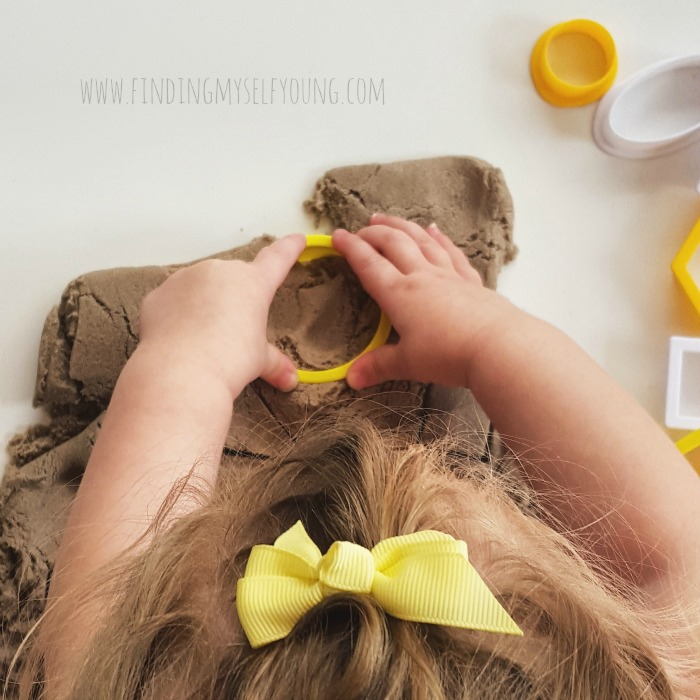 Toddler cutting shapes in kinetic sand