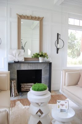 Neutral living room with moulded walls, dueling sofas, a grey fireplace with a large rope mirror on the mantel, and two white coffee tables one is tall and geometric and holds a small bowl of grass the other is shorter and oval shaped