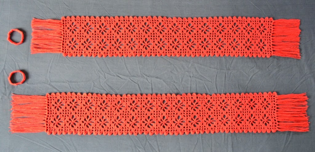 Two red lacy scarves in filet crochet laid out horizontally with respective ring-shaped band fastenings next to them. Long sides have a scallopped edge; short sides have 15 cm straight fringe. The first scarf is at the bottom with 15 rows of spiderweb motifs, 2 per row.  The second scarf is at the top with 14 rows of spiderweb motifs, again the width is 2 motifs per row. The shorter scarf at the top has had its fringe trimmed but the longer one at the bottom  is yet to be trimmed.