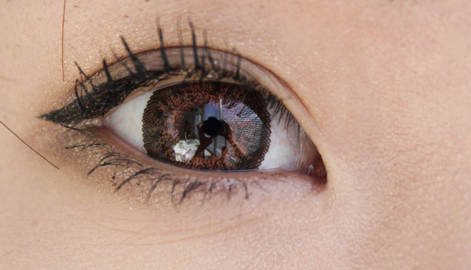 Dark brown eyes with green contacts