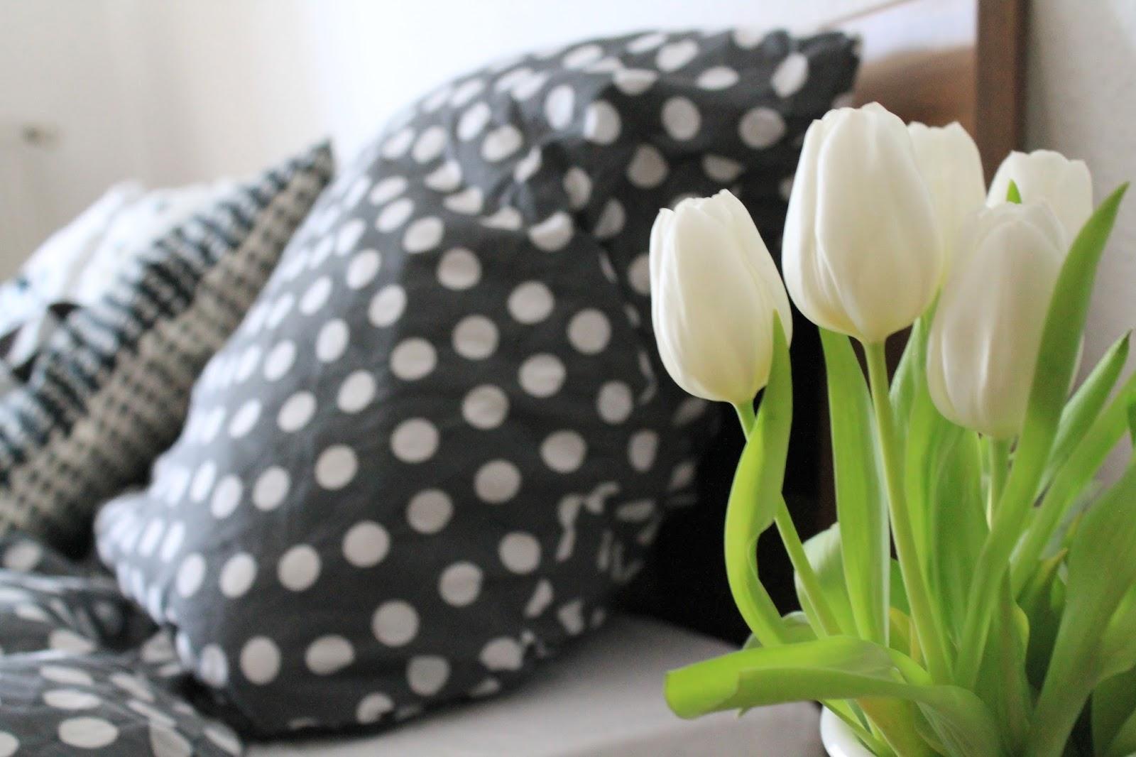 Bett mit Nachttisch und frischen Blumen