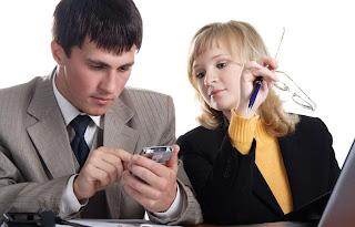 Una pareja mira la pantalla de un celular.