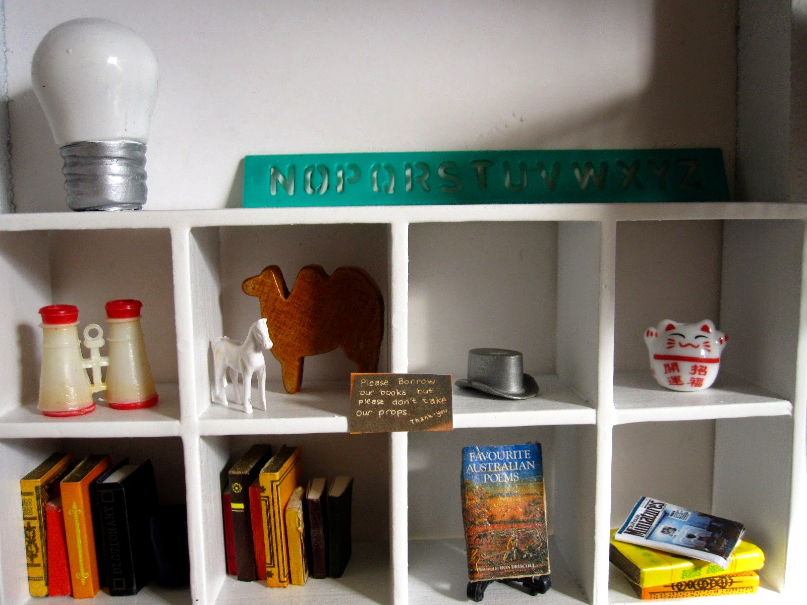 Decor items on a bookcase in a modern dolls' house miniature pop-up Little Library,