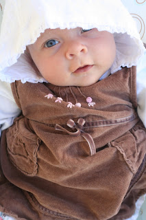 Neve only a few weeks, with her baptism hat and brown Monsoon dress.