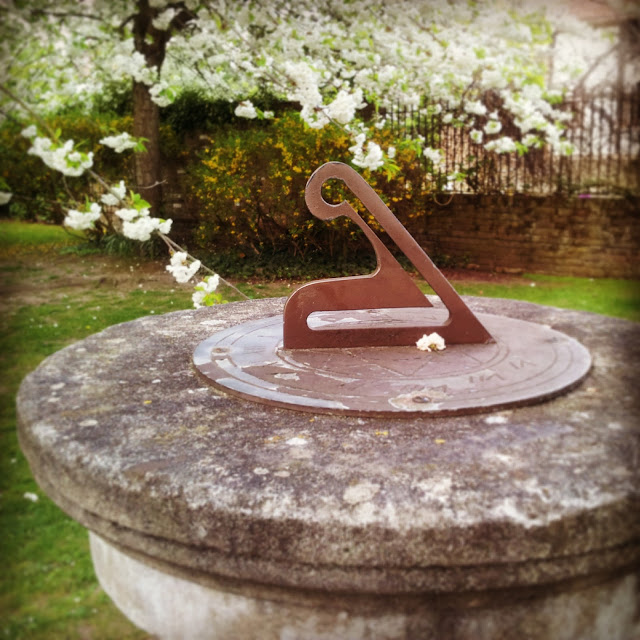 Sundial in a garden surrounded by spring flowers in Walton-on-Thames