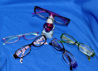 five pairs of reader glasses and a nose eyeglass holder