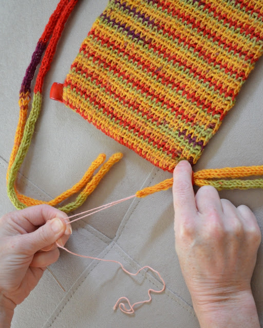 The left hand is pulling on both ends of the thread to pull the drawstring cords through the bead. The right hand is holding the bead still as the cords come through.