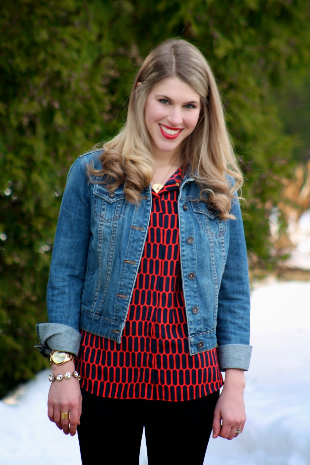 red and navy top with denim jacket, black jeans and cognac riding boots