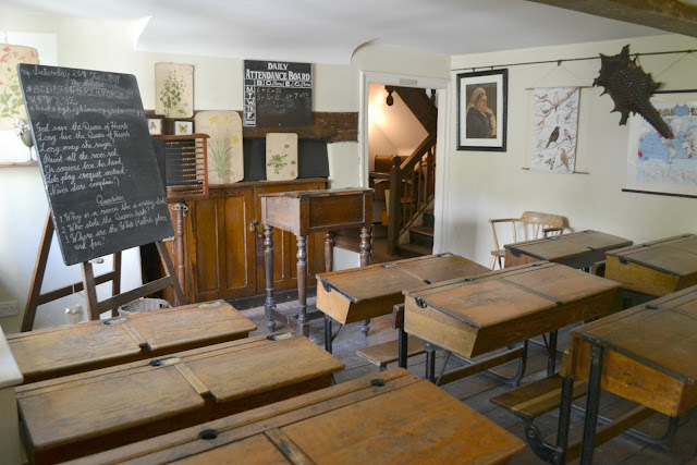 A Victorian school room with blackboard and old-style desks