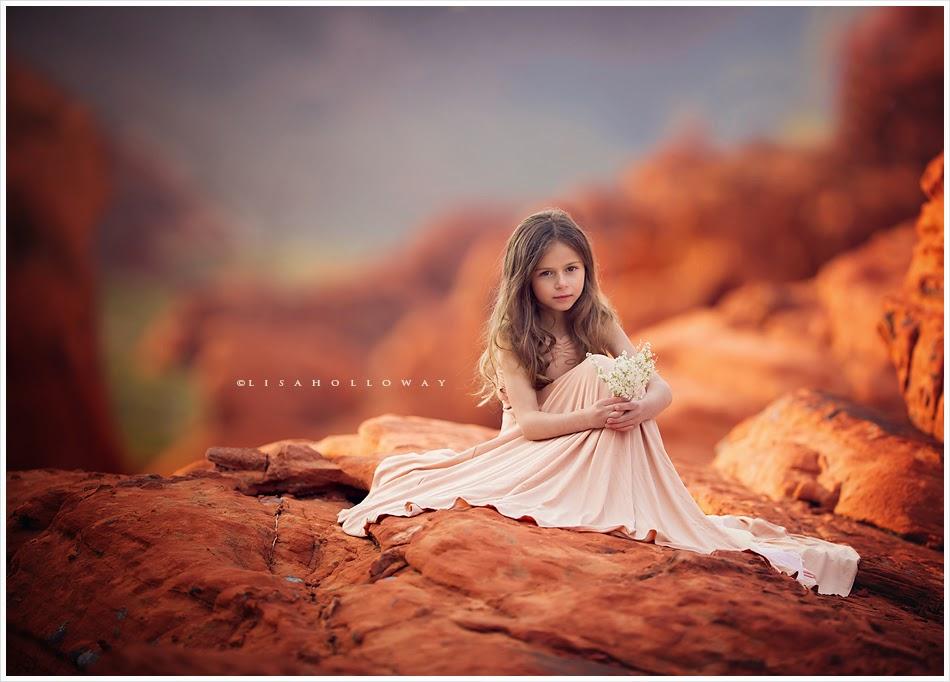 photo de Lisa Holloway représentant une jeune file en grande robe blanche assise sur des rochers