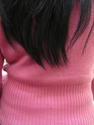 pink sweater and black hair