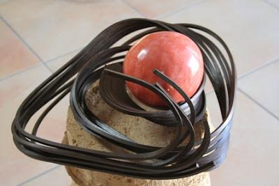 une sculpture en fer forgé_un galet en terre recouvert d'un tadelakt rouge