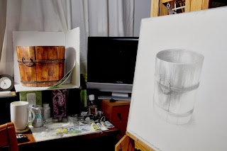 Red water bucket serves as study, easel with artist's orginal graphic being worked on.