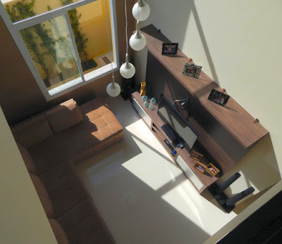Quem acaba de subir a escada que dá acesso para três suítes, te a visão da sala de estar junto ao guarda-corpo de um pequeno mezanino que separa a suíte do casal das duas suítes menores.