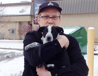 Steve #5 holds his Blue Heeler puppy Holly in a parking lot