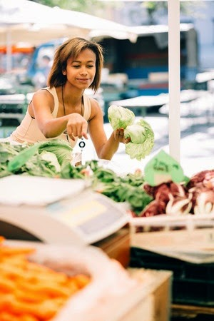 Young woman buyinig produce in a market