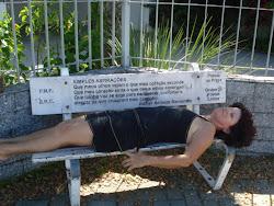 Sandrinha, do Grupo Armação, repousando no banco com poesia, projeto do Grupo de Poetas Livres.
