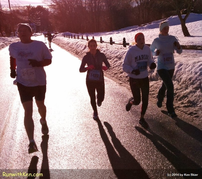 Four runners at a winter race, backlit by the early morning sun--running as they chase their shadows.