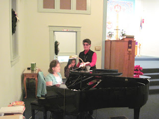 Laurel sings with ten-year-old Taengkwa as ten-year-old Jessie plays the piano.