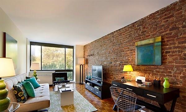 Petit salon avec un mur de brique