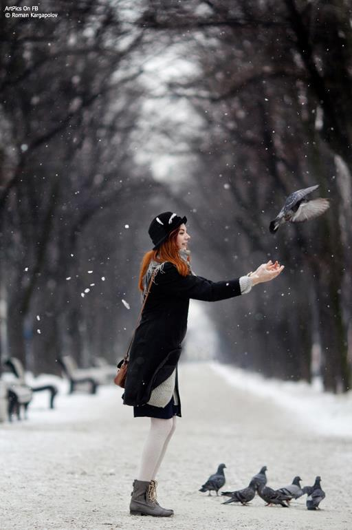 girl playing with pigeon and enjoying rain fall in december