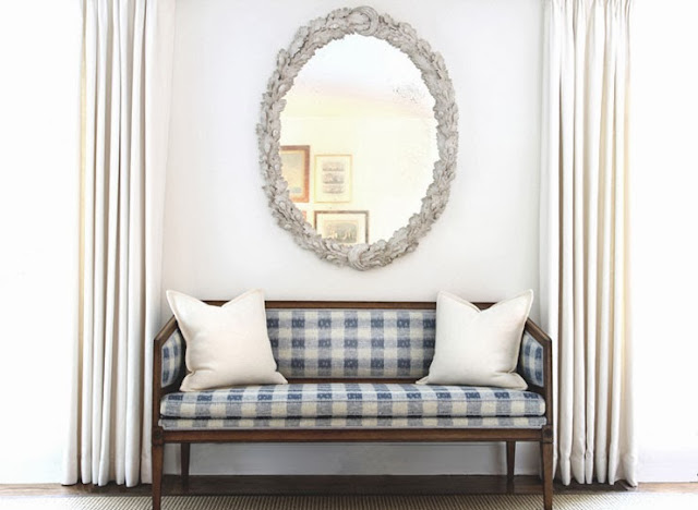 Blue and white gingham bench with white accent pillows and a round mirror with a baroque silver frame