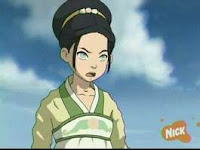 Toph, fair-skinned girl in a long-sleeved robe and band across her chest. Her eyes are pale green with faint pupils, signifying blindness