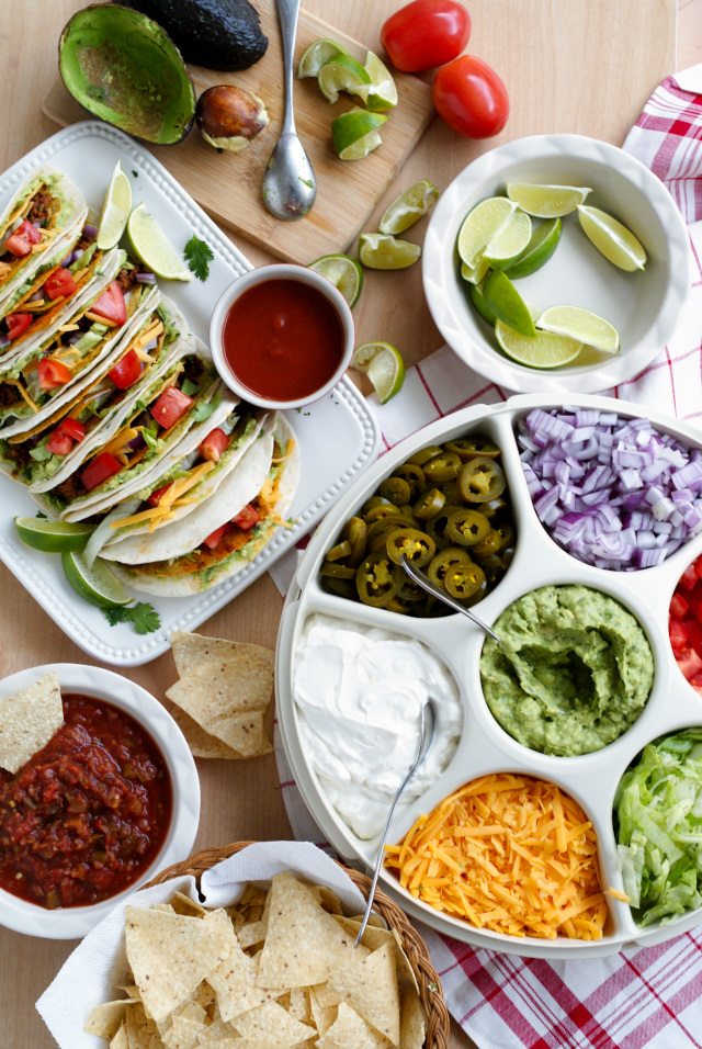 A Guaca-Taco Bar is the ultimate way to feed tacos to a crowd!  Crunchy taco shells are baked in the oven, stuffed with taco meat, and then wrapped with a guacamole smothered flour tortilla to make Guaca-Tacos.  Serve them taco bar-style with all of your favorite classic taco toppings! #GameDayFavorites #OEPGameDay #Sponsored