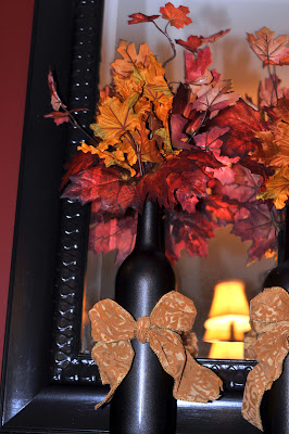 wine bottles along the mantle full of fall leaves and wrapped in orange bows