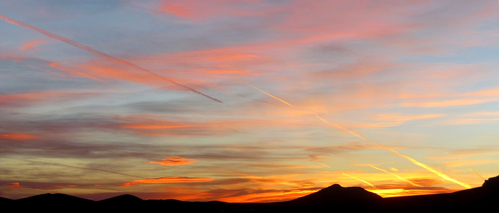 contrails at sunrise over the Peloncillo mountains