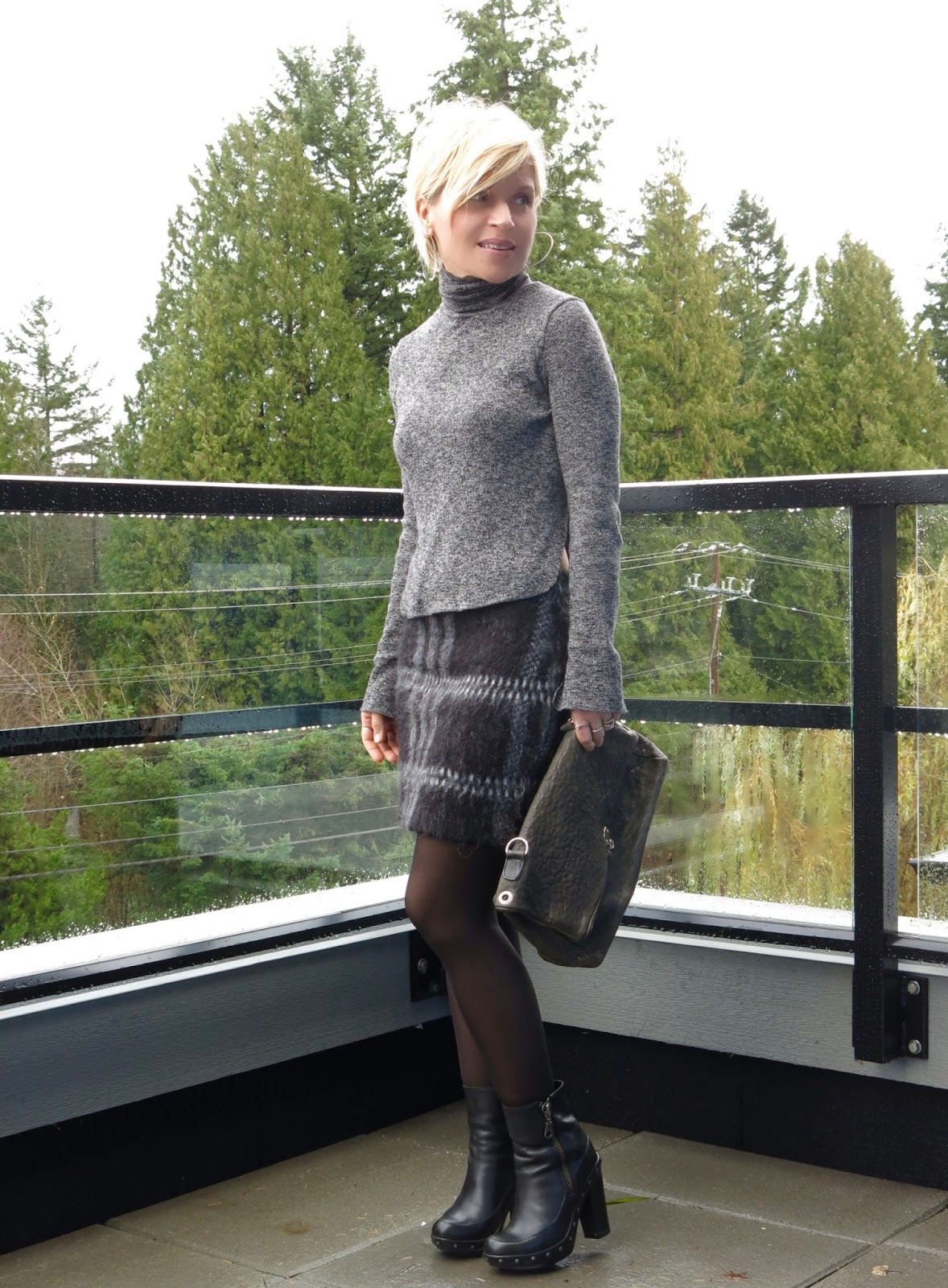 styling a monochromatic look with a turtleneck sweater, plaid mohair skirt, and black tights