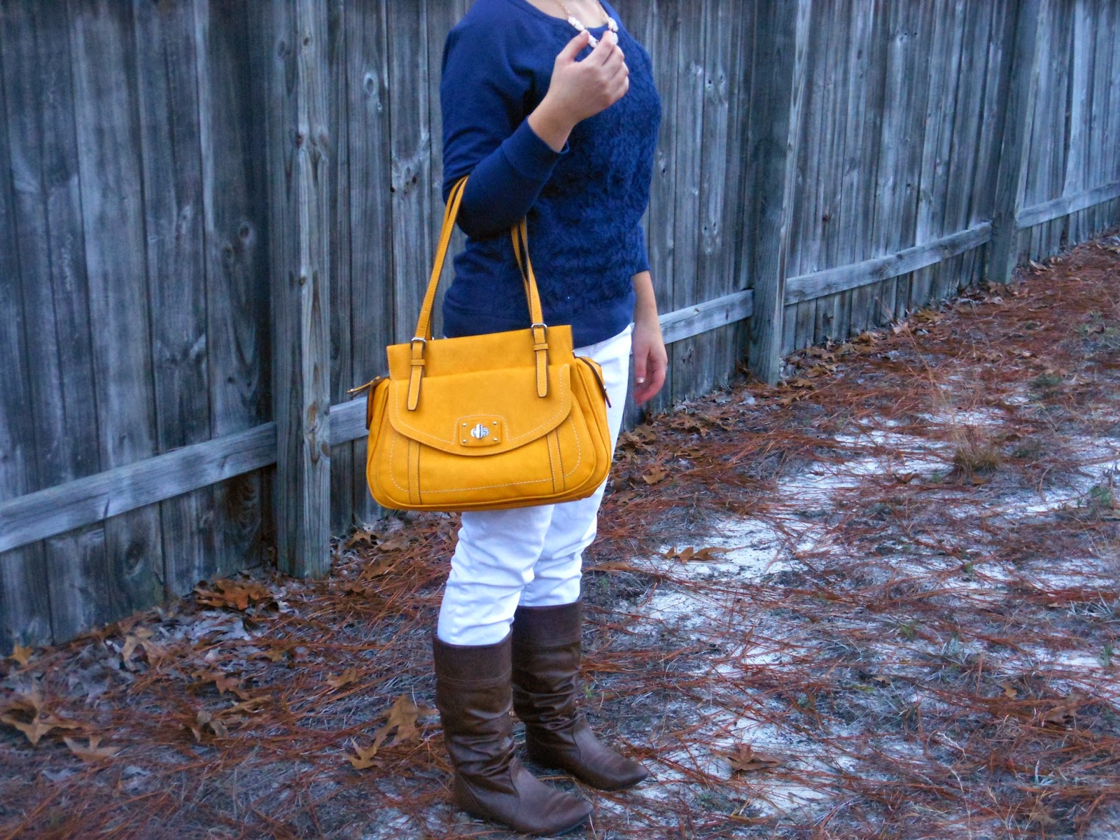Mustard and Navy. Navy lace top, white jeans, brown boots, mustard bag, gold jewelry.