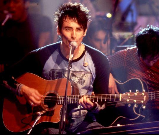 Beto Cuevas cantando acompañado de su guitarra